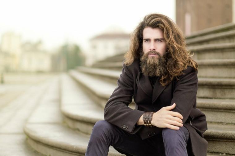 Un uomo seduto su una scalinata con capelli lunghi e barba incolta