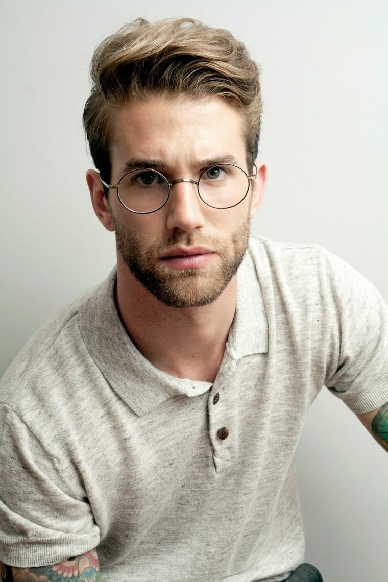 Ragazzo con tatuaggi sul braccio e acconciatura pompadour rasato di lato, barba curata e corta