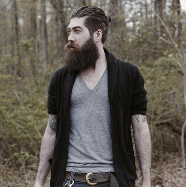 La barba incolta di un uomo con tatuaggi sulle braccia in mezzo ad una foresta