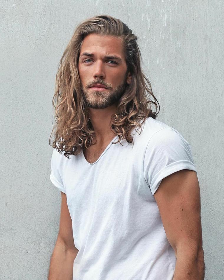 Ragazzo con capelli biondi e lungi, viso con barba corta e baffetti, abbigliamento casual con maglietta bianca