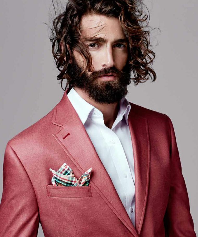 Uomo con capelli castani scompigliati e barba curata leggermente lunga