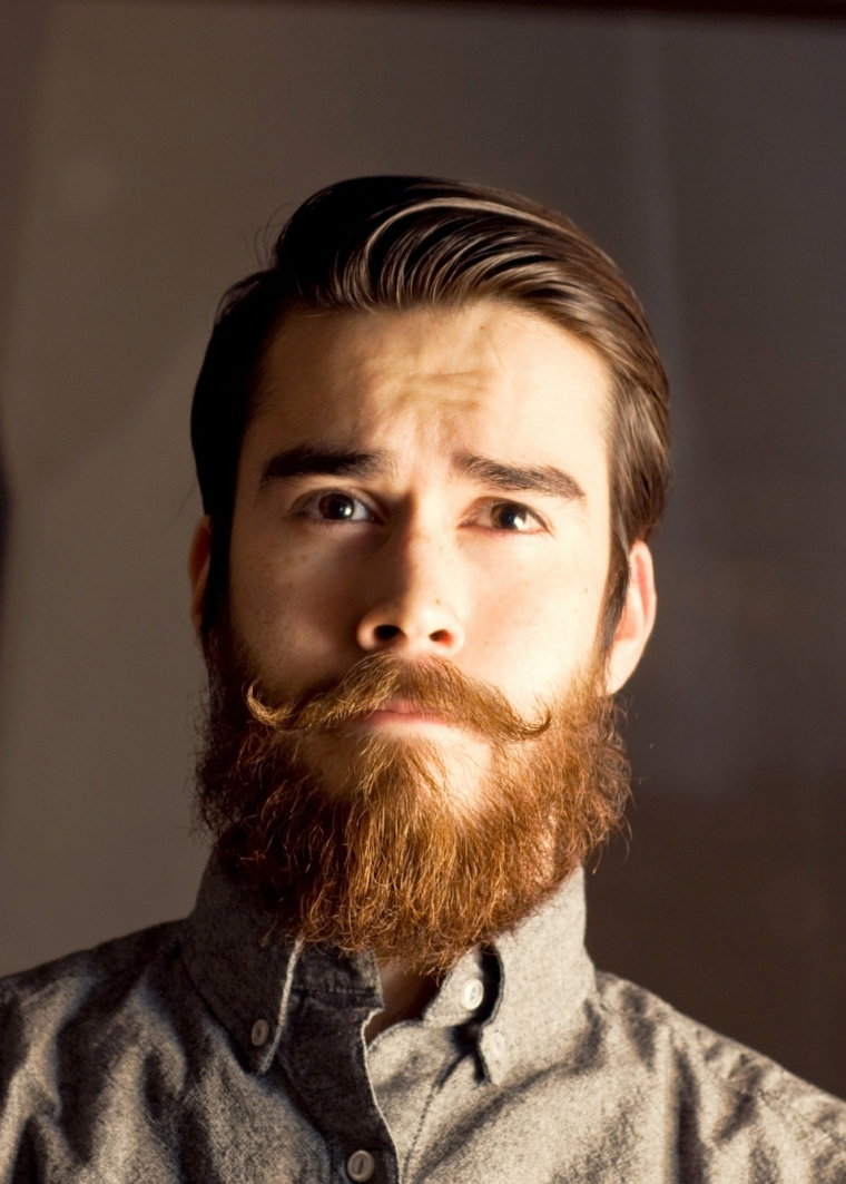 Ragazzo con barba lunga di colore rosso e baffetti vintage, acconciatura pompadour