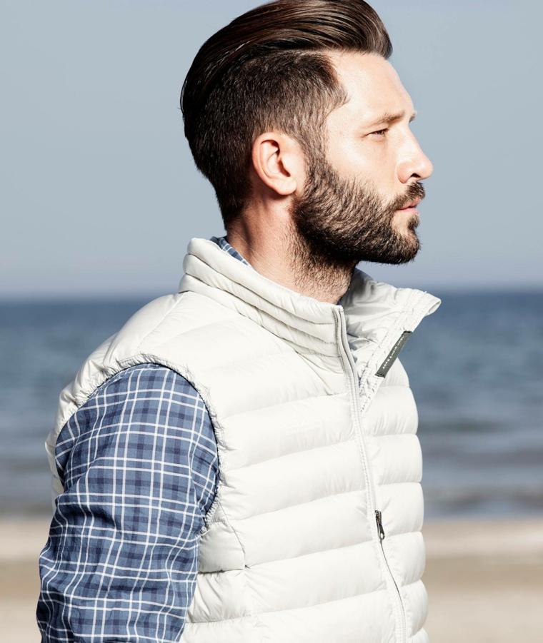 Taglio barba corto di un uomo con capelli rasati ai lati e un'acconciatura pompadour