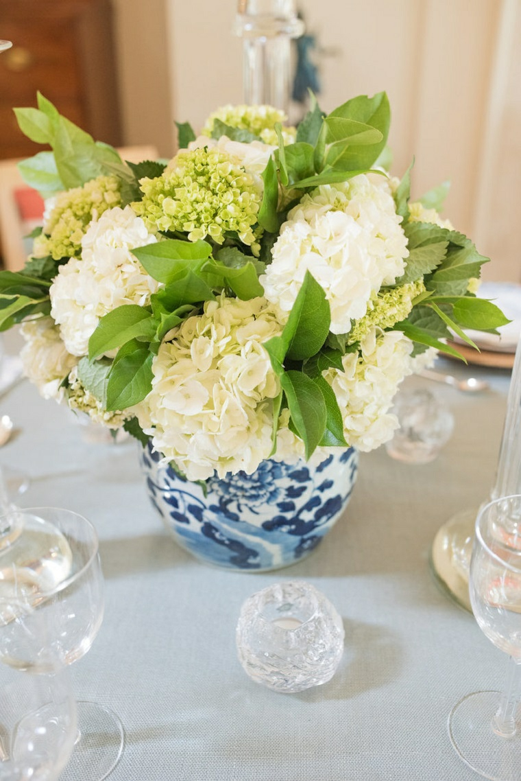 Tavolo nuziale decorato con un vaso di fiori e candele in portacandele di cristallo