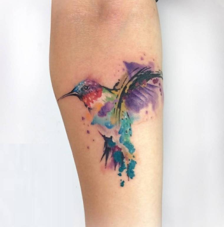 Tattoo avambraccio di una donna e un uccello dai colori vivaci
