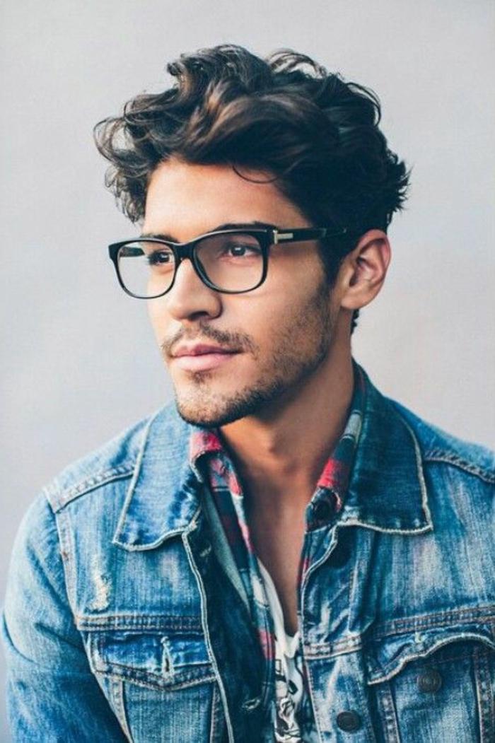 Taglio corto riccio di un ragazzo con gli occhiali da vista, capelli di colore castano dall'effetto mosso
