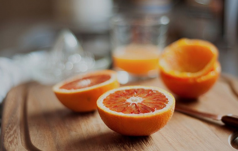 Frutta con meno zuccheri e e spremuta di arancia su un tagliere di legno