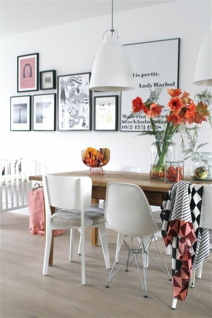 Sala da pranzo decorata con tanti quadri e vasi di fiori freschi