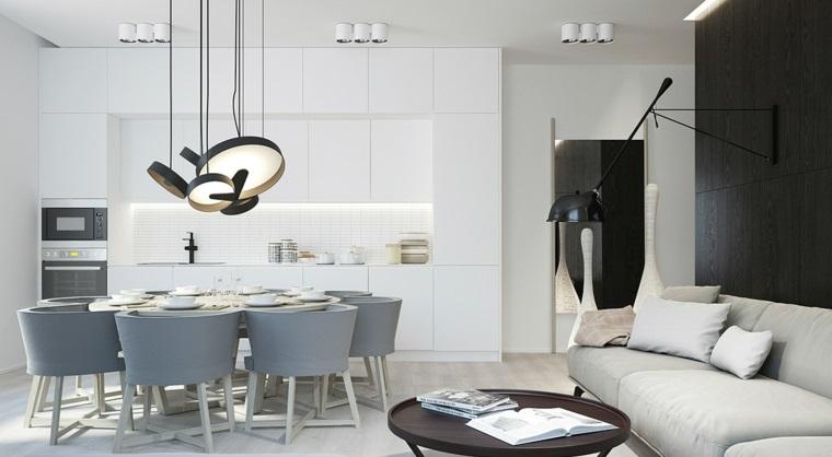 Open space con dei mobili sospesi soggiorno, cucina bianca e lampadari sospesi di colore nero