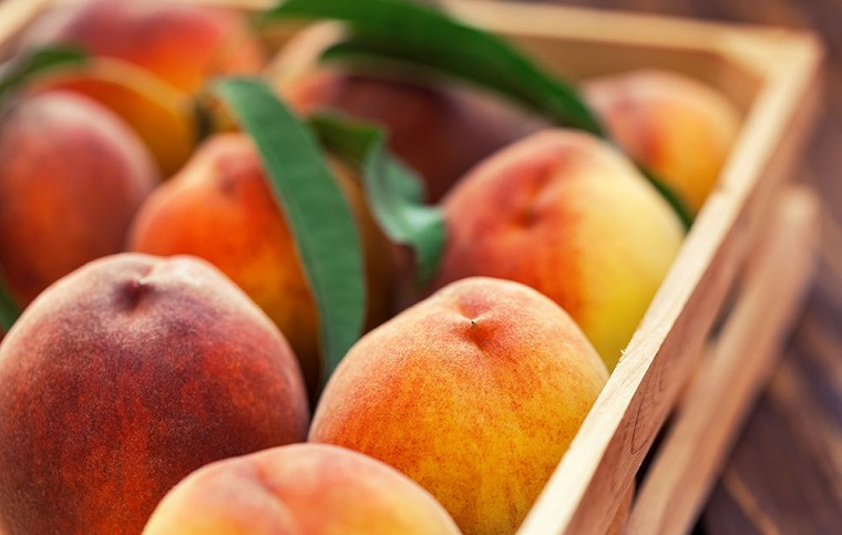 Frutta con meno zuccheri come le pesche, tanti frutti in una cassetta di legno
