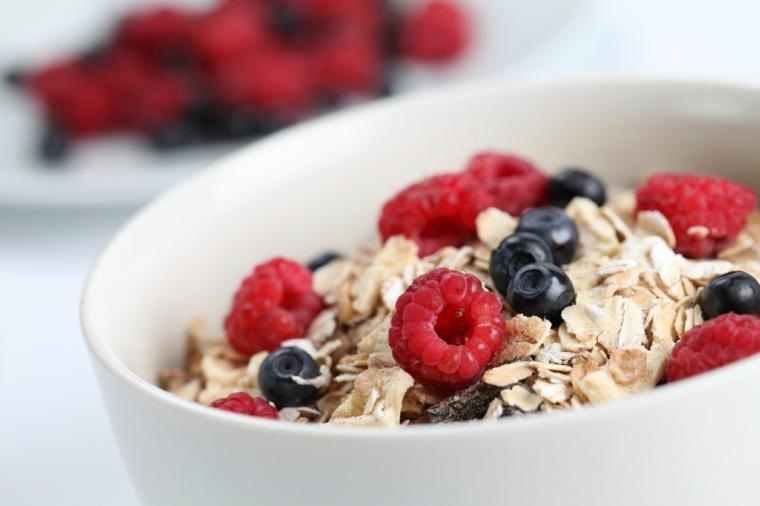 Esempio colazione sana con una ciotola di yogurt con cereali e frutti di bosco