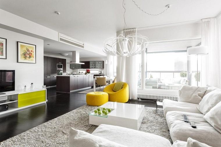 Open space arredato con un divano di colore e tavolino bianco lucido e mele decorative