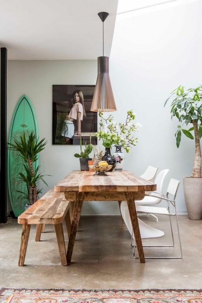 Arredamento sala da pranzo con un tavolo di legno e panchina, decorazione con fiori e un lampadario a sospensione