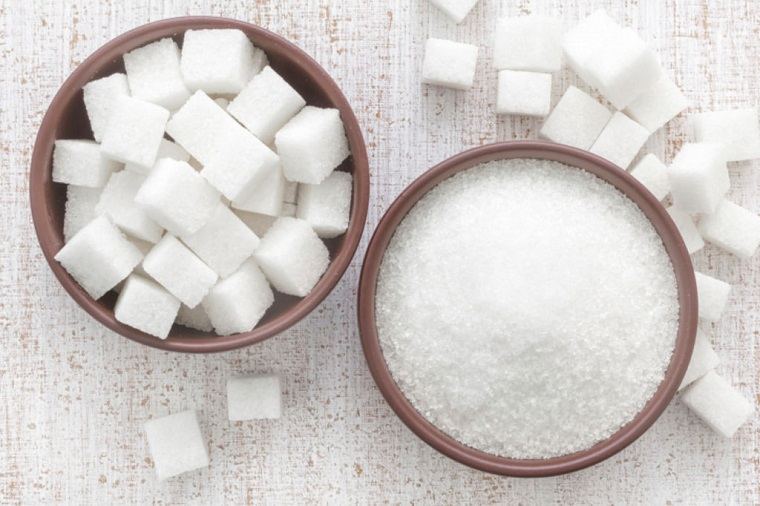Cibi senza carboidrati e cubetti di zucchero in due ciotole di legno