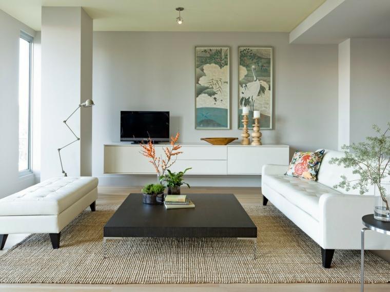 Mobili sospesi soggiorno di colore bianco laccato con decorazioni, divano bianco in pelle e tavolino basso di legno