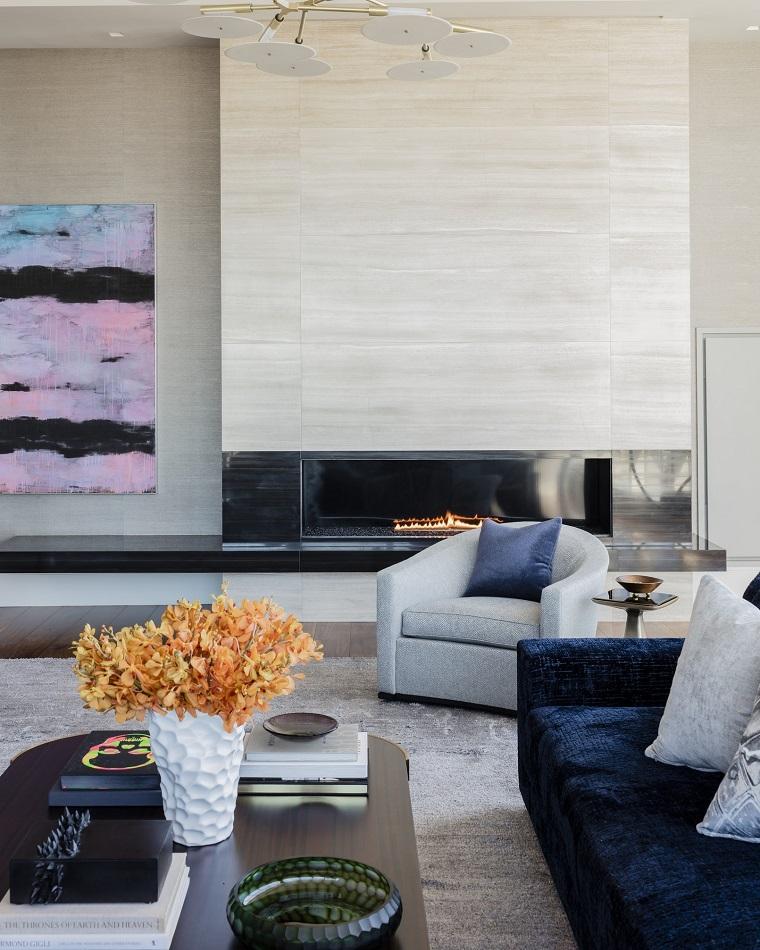 Parete attrezzata con camino in un soggiorno con divano di velluto colore blu e tavolino di legno