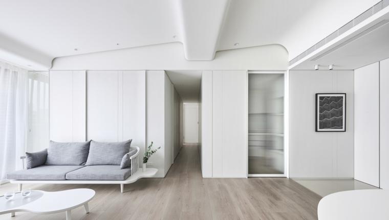Divano di colore grigio con abbinato tavolino, soggiorno con pavimento in legno e pareti bianche