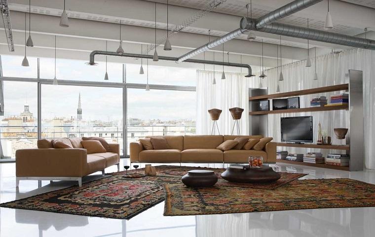 Loft industriale e esempi arredamento soggiorno con divani in pelle e tavolini neri