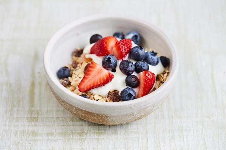 Colazione senza carboidrati e un'idea con cereali e yogurt, frutti di bosco in superficie