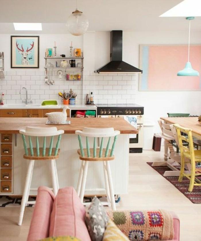 Cucina con open space soggiorno e sala da pranzo con cuscini colorati e pareti bianche