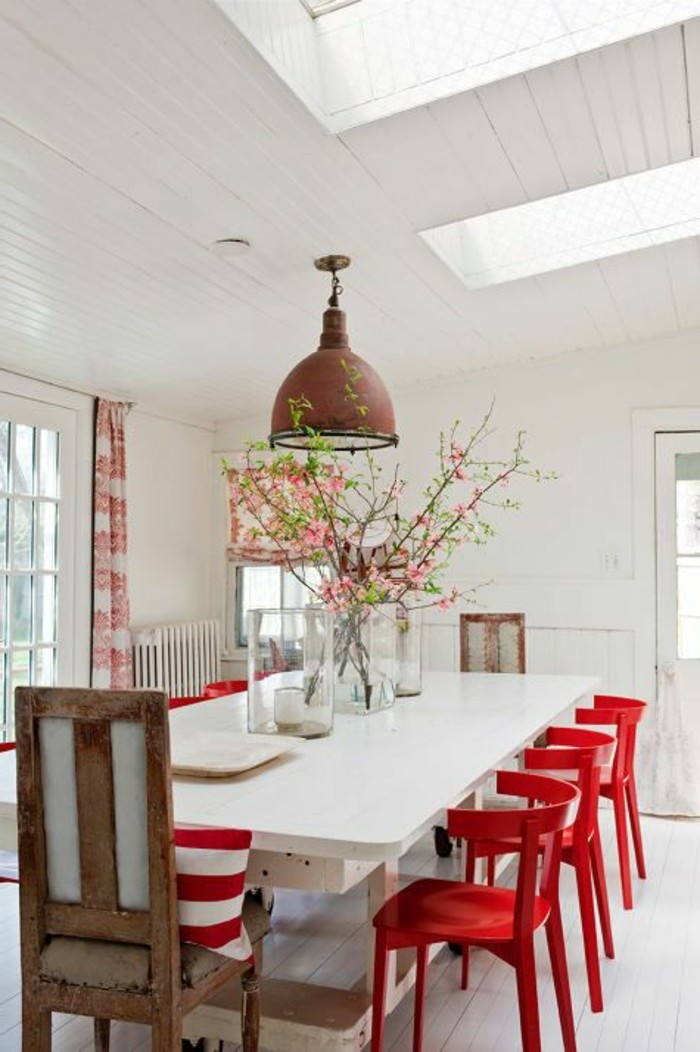 Sala da pranzo con un tavolo grande di colore bianco e sedie rosse