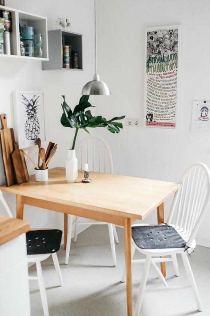 Piccola sala da pranzo con un tavolo di legno, parete decorata con scaffali e quadri artistici
