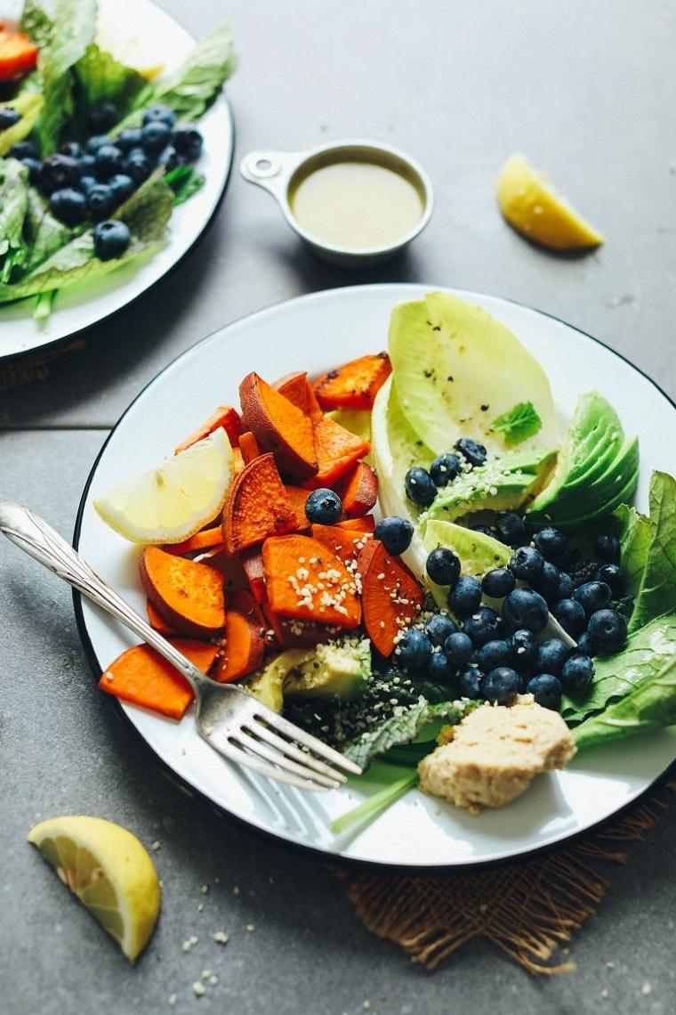 Dieta povera di carboidrati e un piatto con patate dolci, mirtilli e insalata mista
