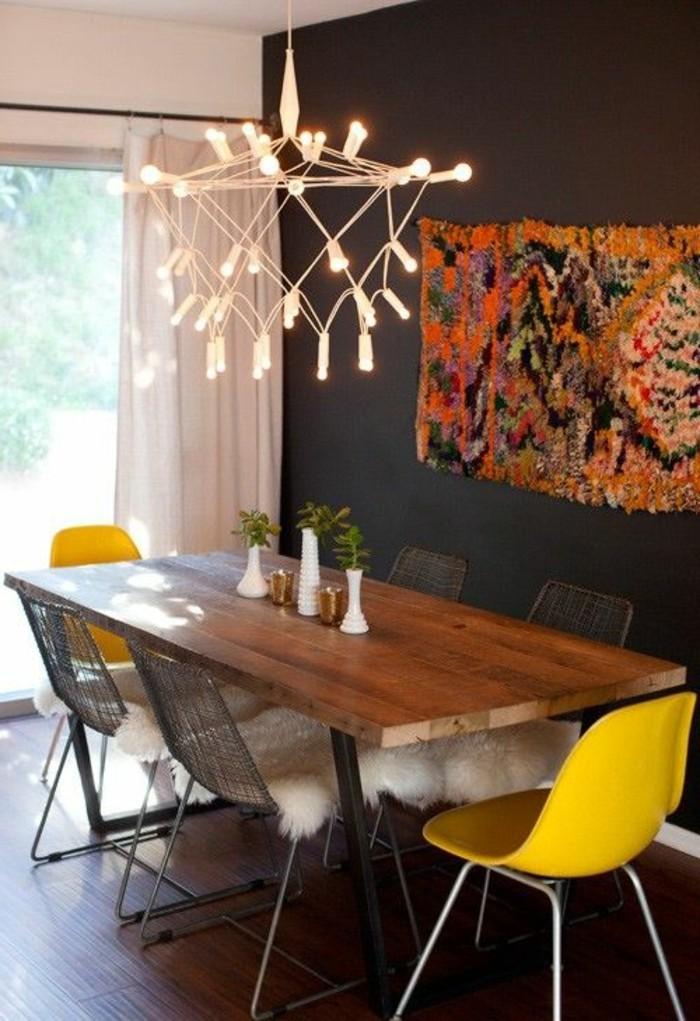 Sala da pranzo con una parete nera e un lampadario di design, arredamento con tavolo di legno e sedie gialle
