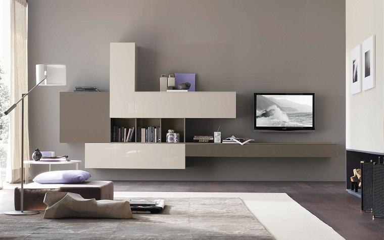 Soggiorno moderno arredato con un mobile sospeso di colore grigio lucido e camino a legna
