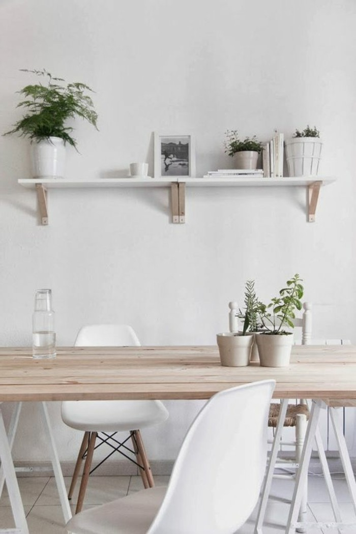 Arredamento sala da pranzo con un tavolo di legno e sedie bianche, parete con mensola e piante verdi
