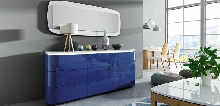 Arredare salotto e sala da pranzo insieme con un mobile lucido di colore blu e tavolo bianco