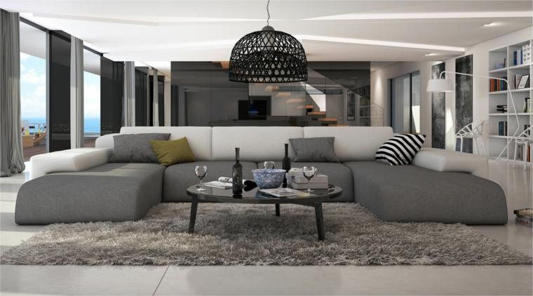 Arredare salotto e sala da pranzo insieme con un divano imbottito di colore grigio e tavolino rotondo