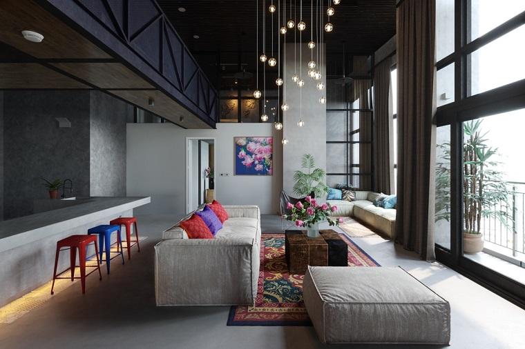 Mobili soggiorno moderni con un divano grigio imbottito decorato con cuscini colorati e lampadine sospese su fili