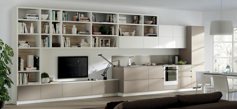 Open space con cucina e parete attrezzata attaccata con libreria e mobile tv di colore beige