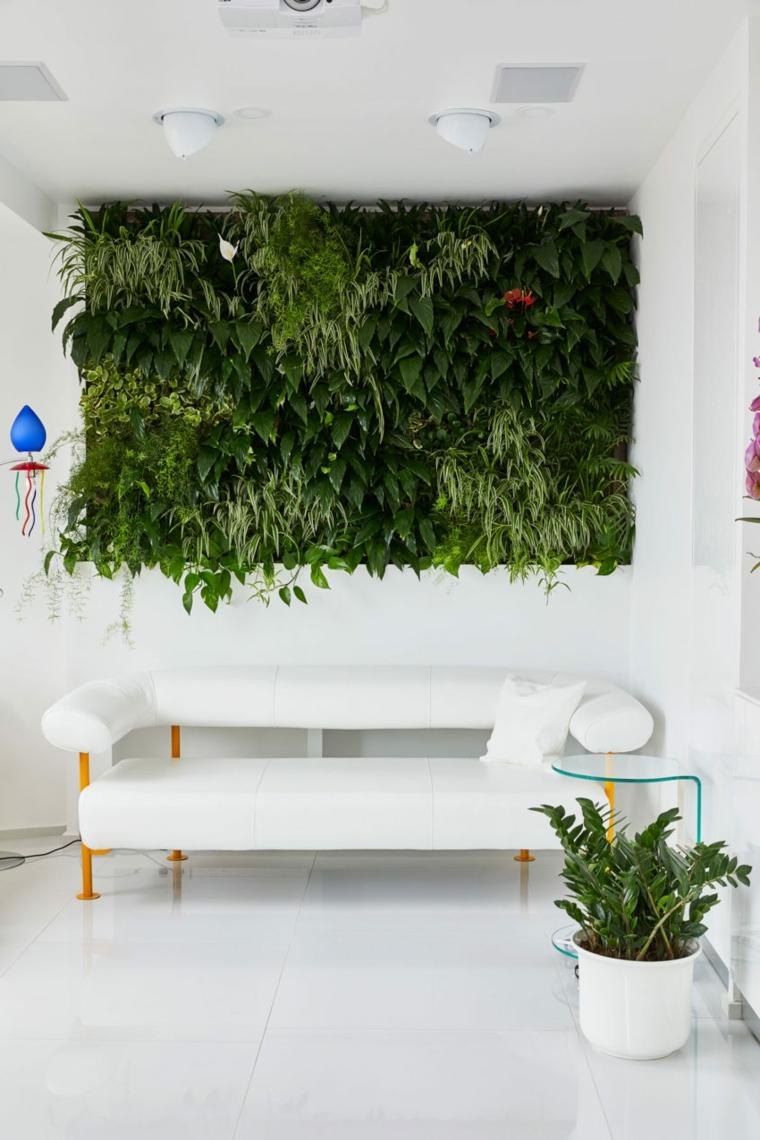 Piccolo soggiorno con un divano bianco e un giardino verticale con piante verdi sulla parete come decorazione