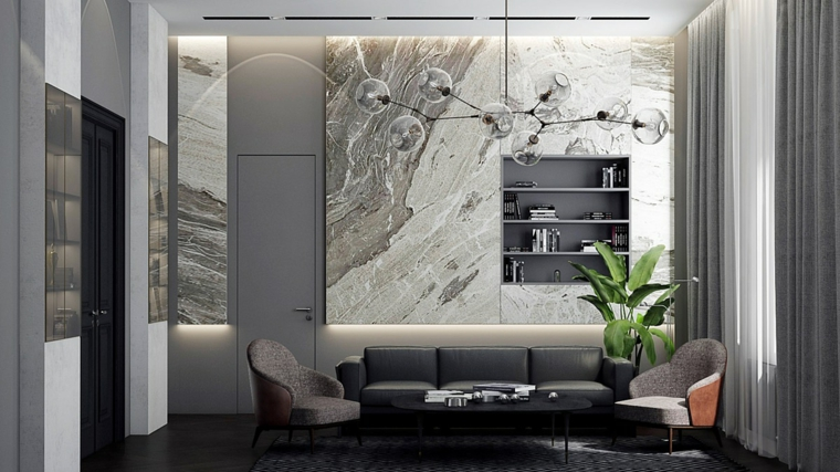 Mobili soggiorno moderni e un divano nero di pelle con due poltrone, parete con pannelli di marmo e lampadario sfere di vetro