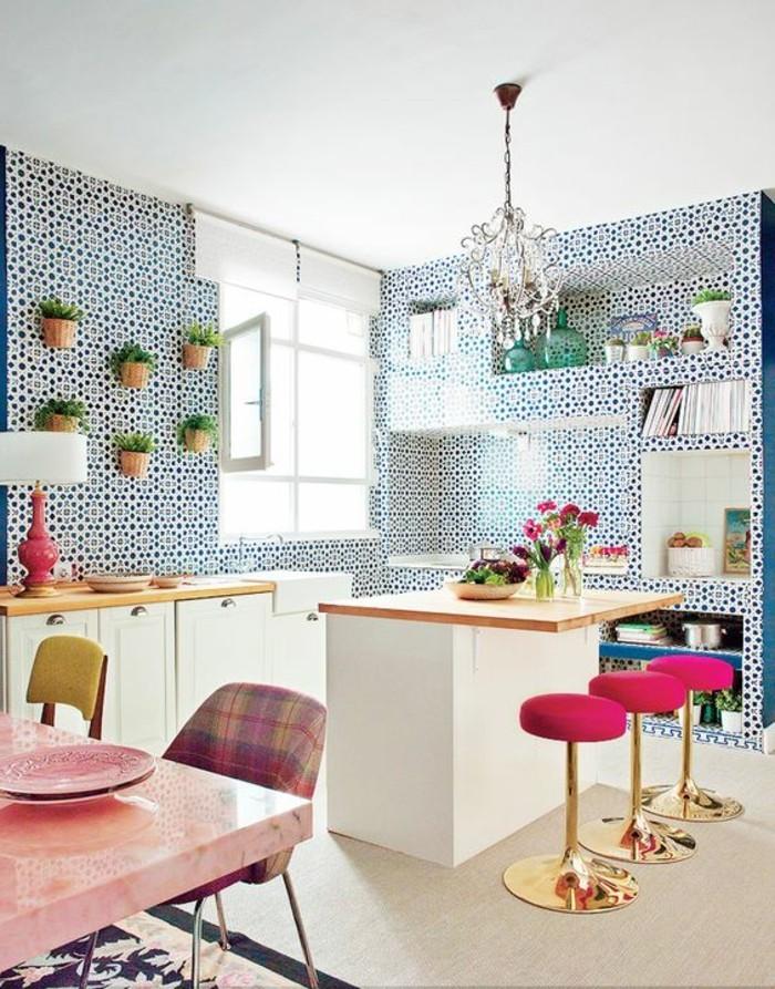 Cucina con mobili di legno e un tavolo da pranzo di colore rosa con sedie colorate