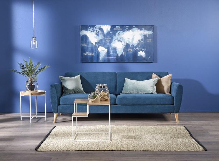 Salotto con pareti di colore blu e un divano di velluto, tavolini di legno con varie decorazioni