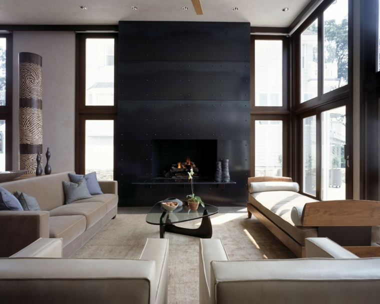Parete attrezzata con camino di colore nero, mobili di colore beige con tavolino di vetro dalla forma particolare