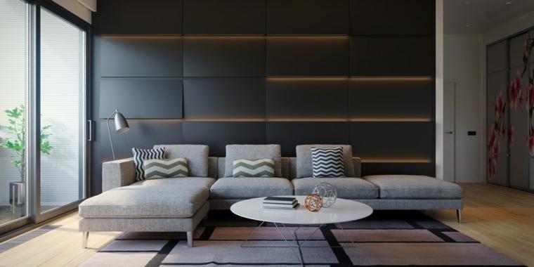 Soggiorno con una parete nera con illuminazione nascosta, divano grigio e tavolino bianco rotondo