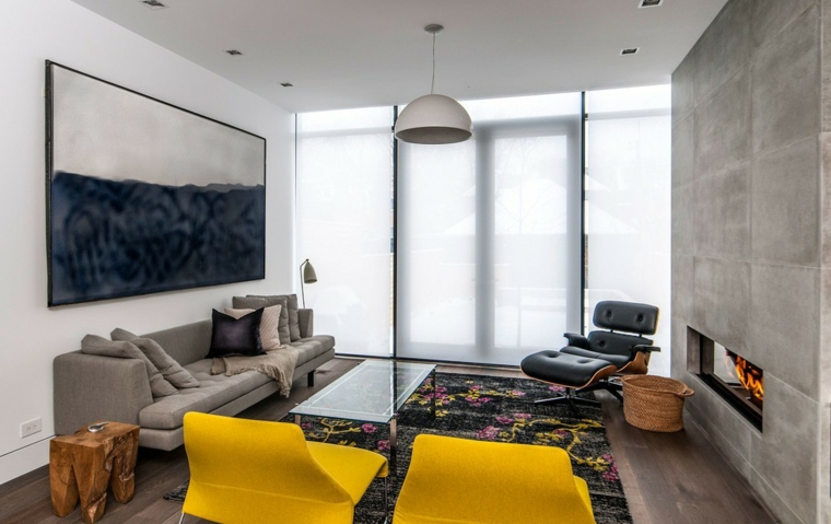 Parete attrezzata con camino di colore grigio, mobili di diverso colore con tappeto motivi floreali