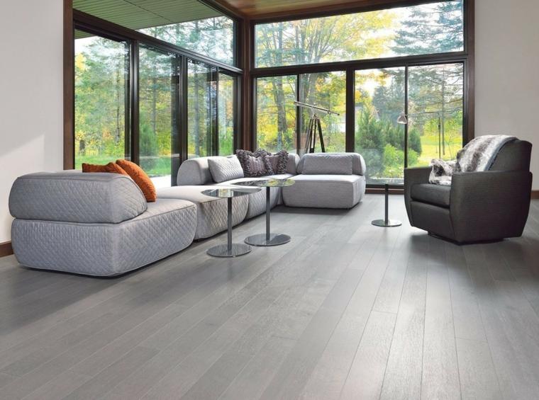 Soggiorni moderni componibili e un'idea con divano imbottito di colore grigio e tavolini alti rotondi