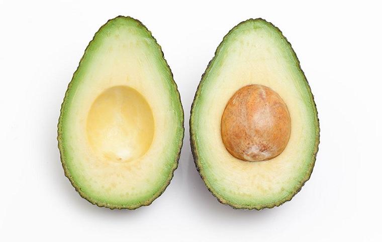 Dieta senza carboidrati e zuccheri mangiando avocado tagliato a metà con la noce
