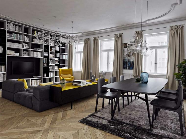 Esempi arredamento soggiorno con un divano nero imbottito e mobili di colore giallo