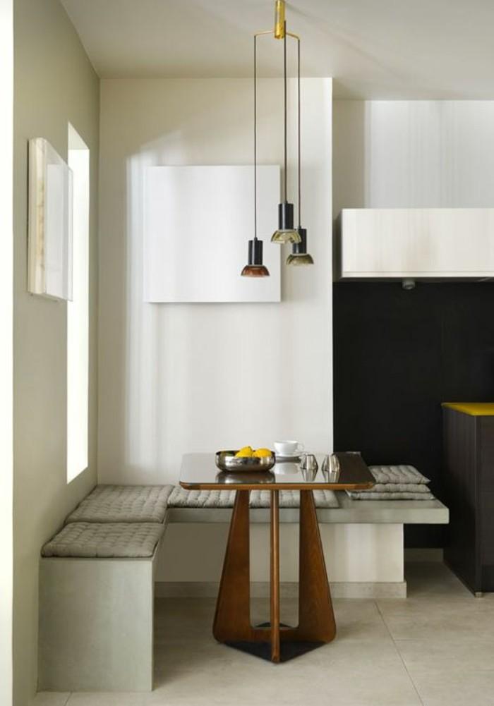 Arredamento sala da pranzo di stile moderno con un divano angolare e tavolino di legno
