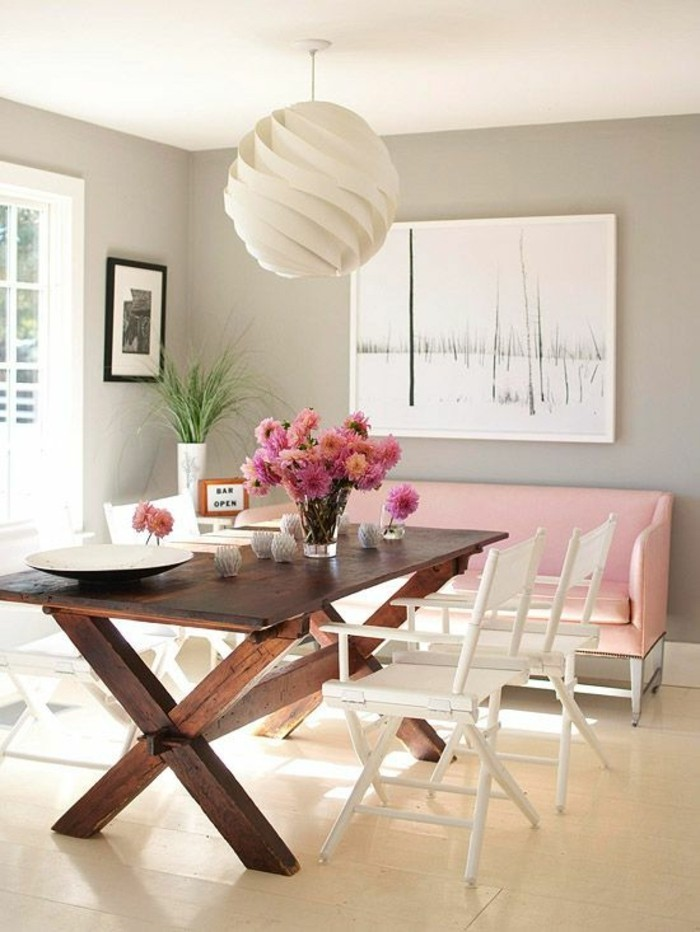 Arredamento sala da pranzo con un tavolo di legno e sedie bianche, accento di colore con un divano rosa