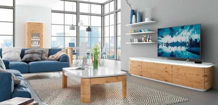 Salotto con mobili di legno dalla superficie bianca e lucida, divano angolare imbottito di colore blu