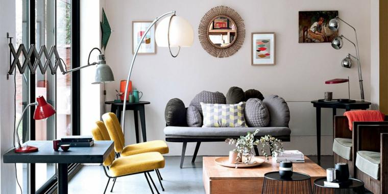 Soggiorno con un divano e sedie di colore giallo, arredamento con tavolini di legno