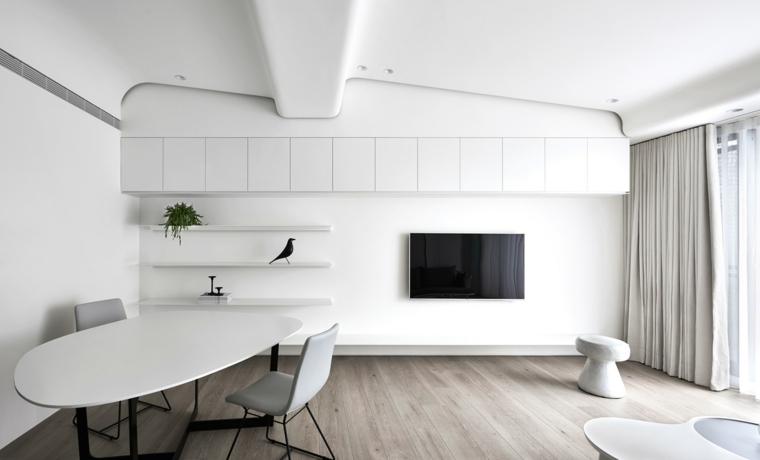 Soggiorno minimal con mobili sospesi di colore bianco e tv appesa alla parete