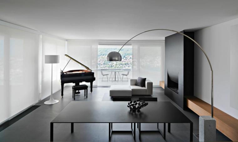 Parete attrezzata con camino di colore nero con divano bianco e tavolo da pranzo in metallo